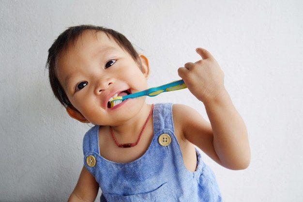 happy-asian-baby-girl-practice-brushing-her-teeth_75876-30
